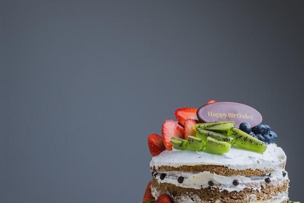 Bolo de frutas frescas de feliz aniversário com chocolate feliz aniversário no conceito de bolo com bolo de frutas kiwi de morango. comida