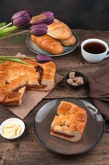 Bolo de frutas, pães e um buquê de tulipas em um fundo de madeira.