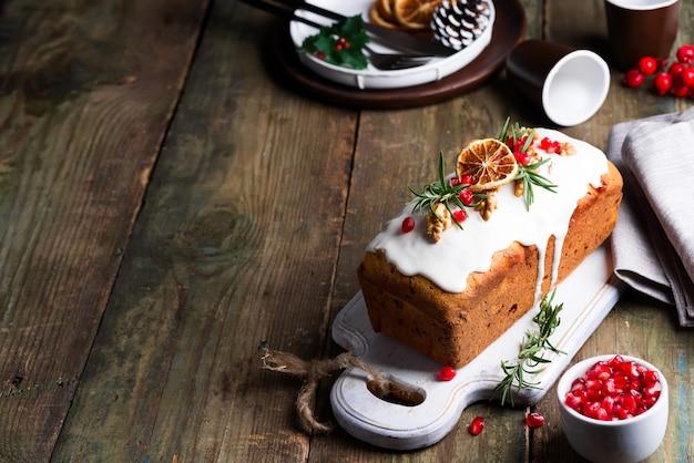 Bolo de frutas polvilhado com glacê, nozes, grãos de romã e laranja seca de madeira velha. bolo caseiro de férias de natal e inverno