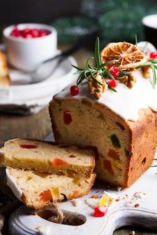 Bolo de frutas polvilhado fatiado com glacê, nozes, grãos de romã e close-up laranja seco. bolo caseiro de férias de natal e inverno