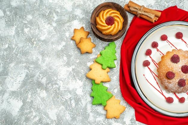Bolo de frutas vermelhas em uma placa oval branca biscoitos de cinamon xale vermelho em uma superfície cinza