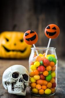 Bolo de halloween aparece, crânio e doces coloridos na parede de madeira rústica