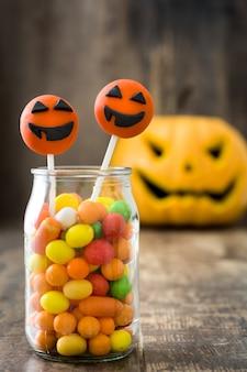 Bolo de halloween aparece e doces coloridos na parede de madeira rústica