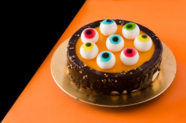 Bolo de halloween com decoração de olhos doces em laranja e preto.