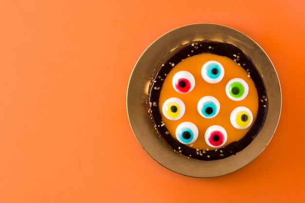Bolo de halloween com decoração de olhos doces em laranja