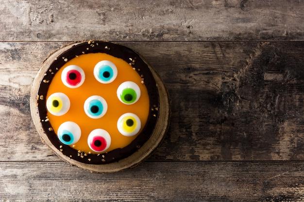 Bolo de halloween com decoração de olhos doces na mesa de madeira. vista do topo. copie o espaço