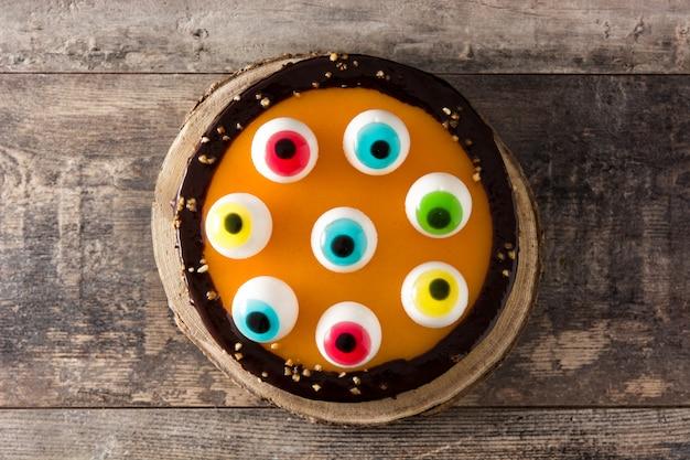 Bolo de halloween com decoração de olhos doces na mesa de madeira. vista do topo