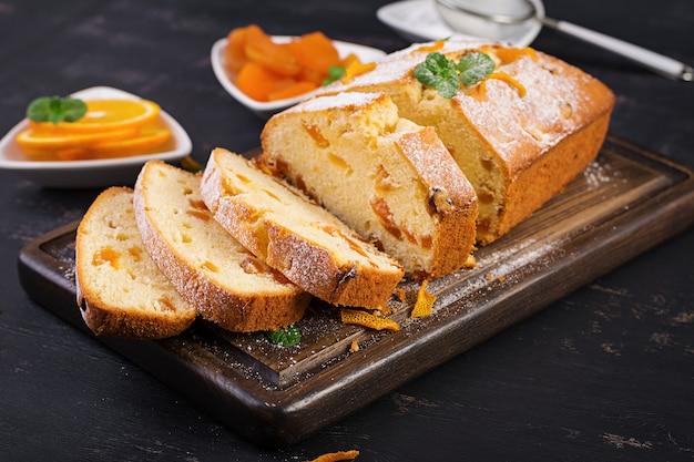 Bolo de laranja com damascos secos e açúcar em pó