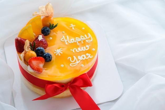 Bolo de laranja com feliz ano novo e coberto com laranja, morango, mirtilo e groselha do cabo em um pano branco, espaço de cópia e conceito de sobremesa