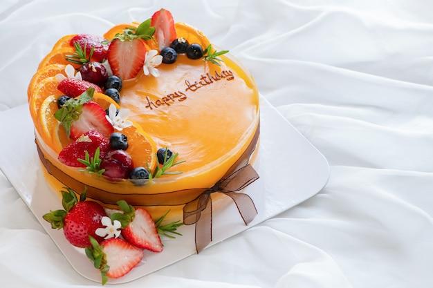 Bolo de laranja com feliz dia de nascimento e coberto com laranja, morango, mirtilo na superfície de um pano branco, espaço de cópia e conceito de sobremesa