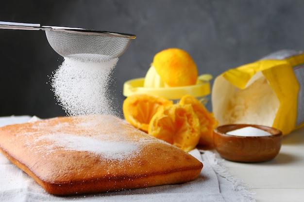 Bolo de laranja decorando açúcar em pó e ingredientes no fundo