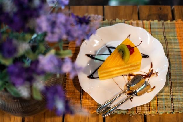 Bolo de laranja em prato branco na mesa de madeira