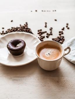 Bolo de lava choco no prato com uma xícara de café e grãos de café torrados