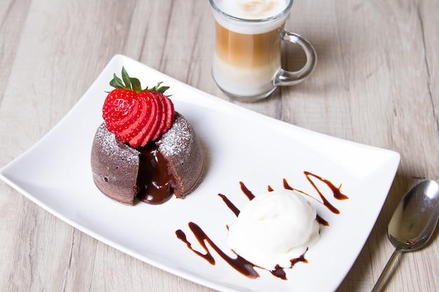 Bolo de lava de fondant de chocolate com morangos e sorvete