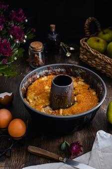 Bolo de maçã na mesa de madeira escura, ovos, canela, extrato de baunilha