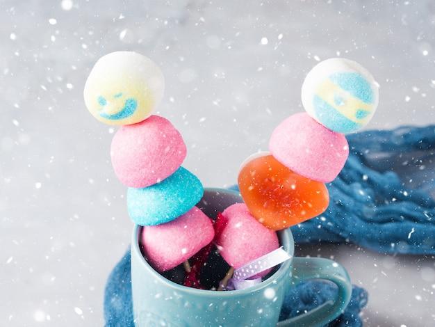Bolo de marshmallows colorido aparece rosto masculino e feminino