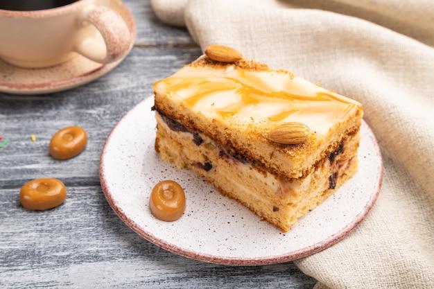 Bolo de mel com creme de leite, caramelo, amêndoas e uma xícara de café em uma superfície de madeira cinza e tecido de linho