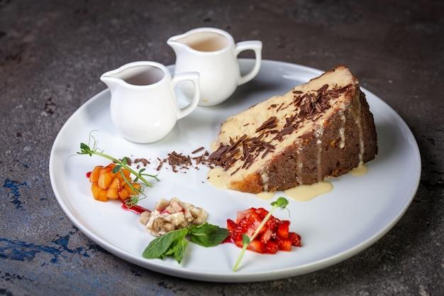 Bolo de mel com gotas de chocolate e frutas vermelhas em um café em um prato branco