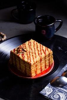 Bolo de mel com porções quadradas, decorado com calda de morango