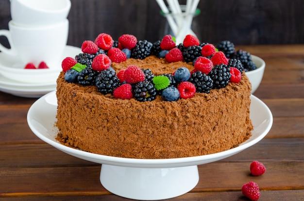 Bolo de mel de chocolate com creme e frutas frescas em cima de um prato branco sobre um fundo de concreto. copie o espaço.