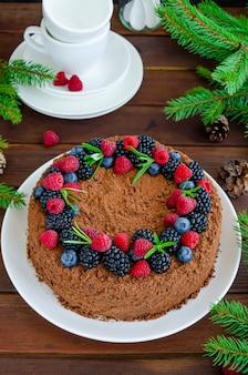 Bolo de mel de chocolate com creme e frutas frescas por cima em um prato branco sobre um fundo de madeira. bolo de natal e ano novo. copie o espaço.
