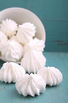 Bolo de merengue branco espalhado sobre um fundo azul de madeira