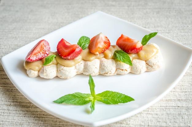 Bolo de merengue com creme e morangos frescos