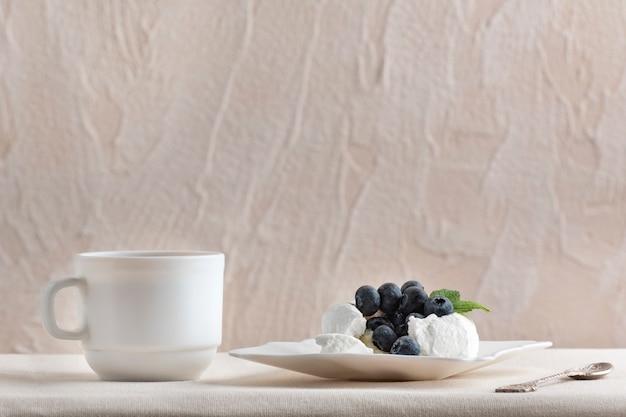 Bolo de merengue decorado com mirtilos ao lado do copo branco. sobremesa deliciosa.