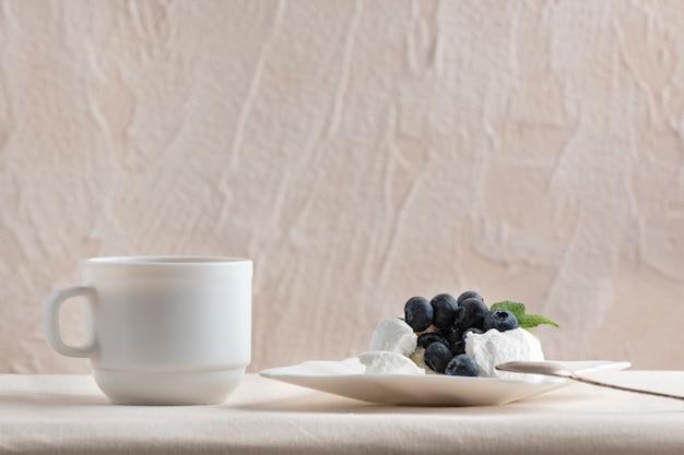 Bolo de merengue decorado com mirtilos e café. sobremesa deliciosa.