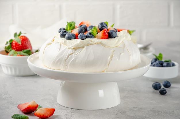 Bolo de merengue pavlova com chantilly e frutas frescas por cima em um prato sobre um fundo cinza de concreto.