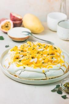 Bolo de merengue pavlova com manga fresca e maracujá e chantilly sobre fundo de ardósia, pedra ou concreto
