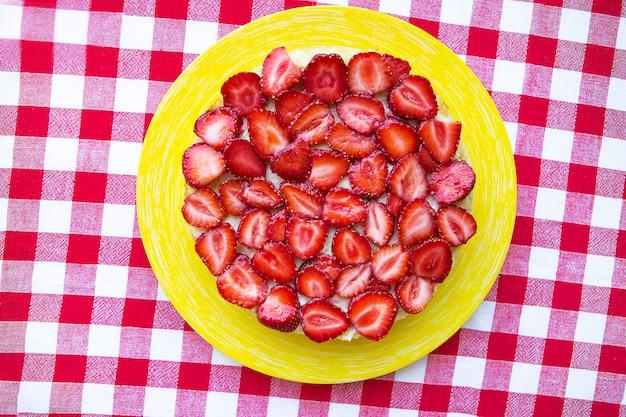 Bolo de morango brilhante e delicioso num guardanapo vermelho em uma gaiola