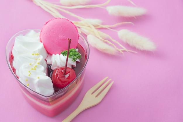 Bolo de morango colorido e macaron em fundo rosa