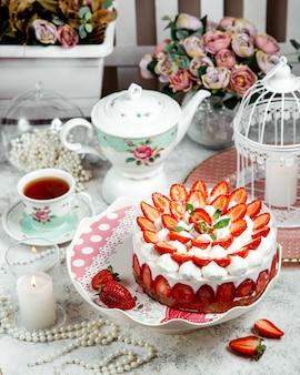 Bolo de morango decorado com morangos fatiados e um chá preto