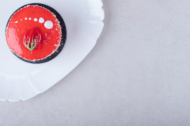 Bolo de morango e bolachas cobertas de chocolate em um prato na mesa de mármore.
