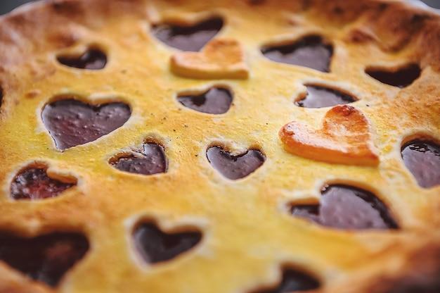 Bolo de morango no dia dos namorados com corações em um fundo de madeira