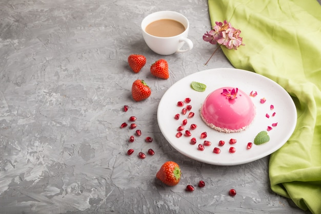 Bolo de mousse rosa com morango e uma xícara de café em uma superfície de concreto cinza. vista lateral, copie o espaço.