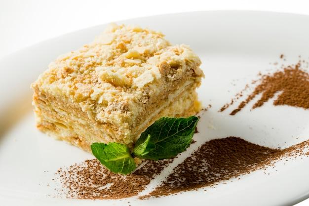 Bolo de napoleão com folha de hortelã no prato branco