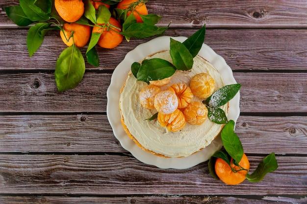 Bolo de natal com tangerinas frescas inteiras em superfície de madeira rústica