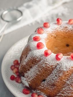 Bolo de natal em forma de uma coroa de flores com açúcar em pó e sementes de romã num prato branco