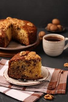 Bolo de nozes caseiro americano está localizado em uma superfície escura, o pedaço de bolo em primeiro plano