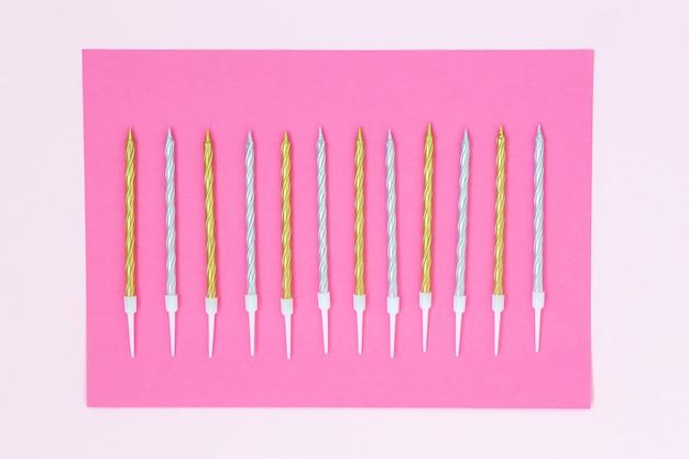 Bolo de ouro e prata velas em um fundo rosa