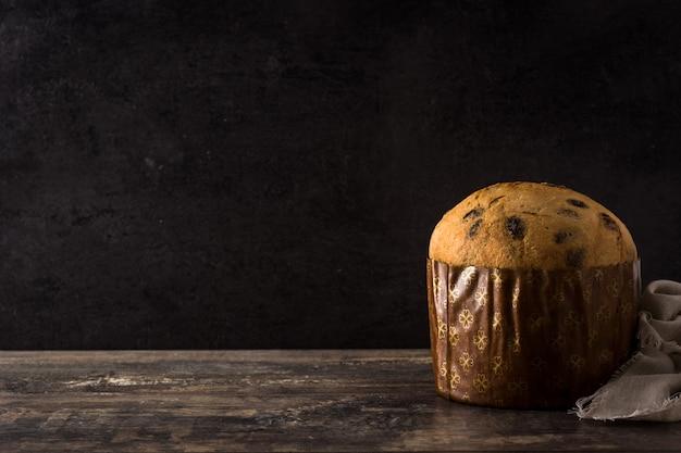 Bolo de panetone de chocolate de natal com natal decorado na mesa de madeira copie o espaço