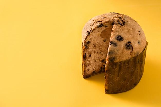 Bolo de panetone de chocolate de natal isolado fundo amarelo espaço para texto