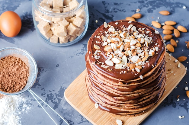 Bolo de panqueca. uma pilha de panquecas de chocolate com creme de chocolate e amêndoas por cima.