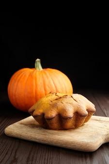 Bolo de pão caseiro de abóbora na tábua de madeira com abóbora fresca em fundo preto. refeições de ação de graças.