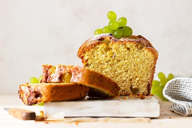 Bolo de pão com polenta, uva, tomilho e açúcar de confeiteiro na placa de madeira branca.