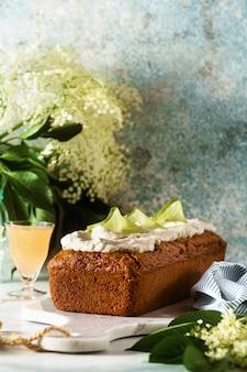 Bolo de pão doce de verão em uma mesa com flores e uma bebida em copos. com creme de coco e limão. sobremesa para brunch ou café da manhã