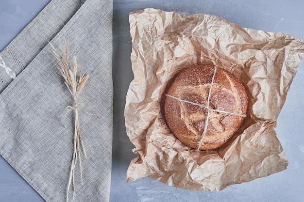 Bolo de pão redondo feito à mão em um pedaço de papel.
