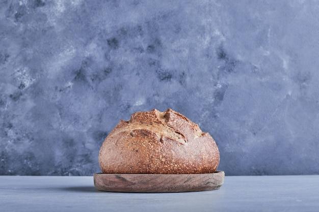 Bolo de pão redondo feito à mão na bandeja de trigo, vista lateral.